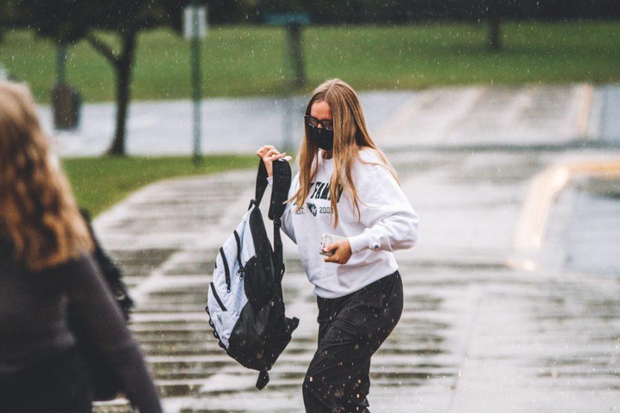 A freshman walks through the rain on her way into orientation. Collin Nawrocki - The Phoenix