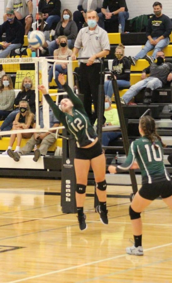 Holy Family's Zoe Schuele '24 (12) setting the ball up to hit against Hutchinson