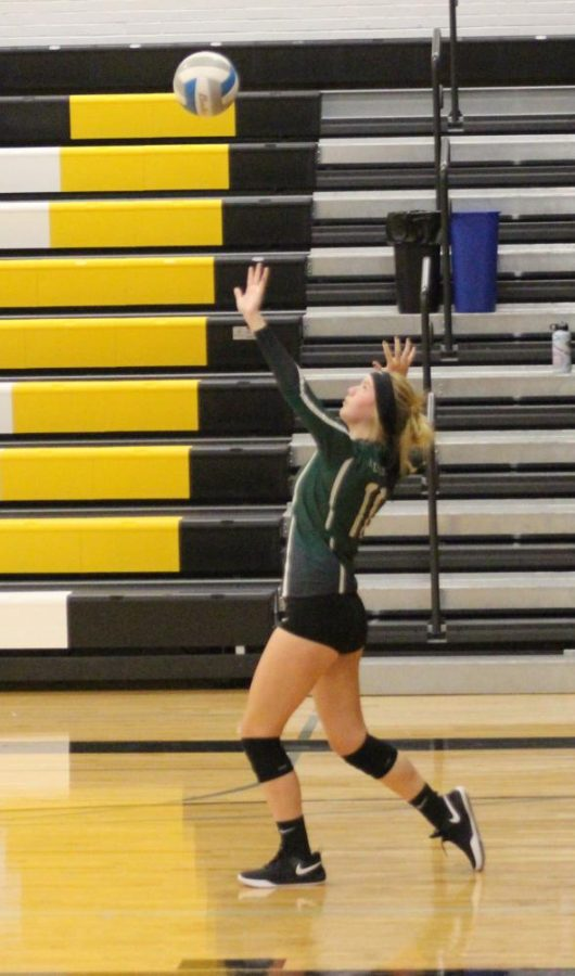 Holy Family's Captain Tatum Hussey '22 (11) serving the ball against Hutchinson